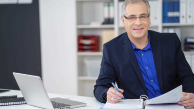 Businessman taking notes in office - Leadership | Amarex
