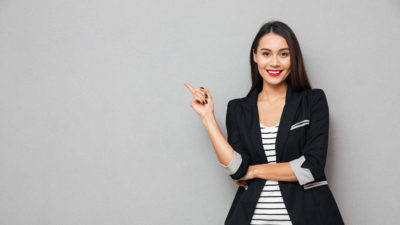 Smiling Business Woman Pointing Finger Up and Looking at the Camera - Therapeutic Areas | Amarex