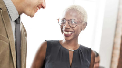 Business woman smiling in meeting - History | Amarex